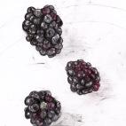 Three Black Berries on a White China Plate